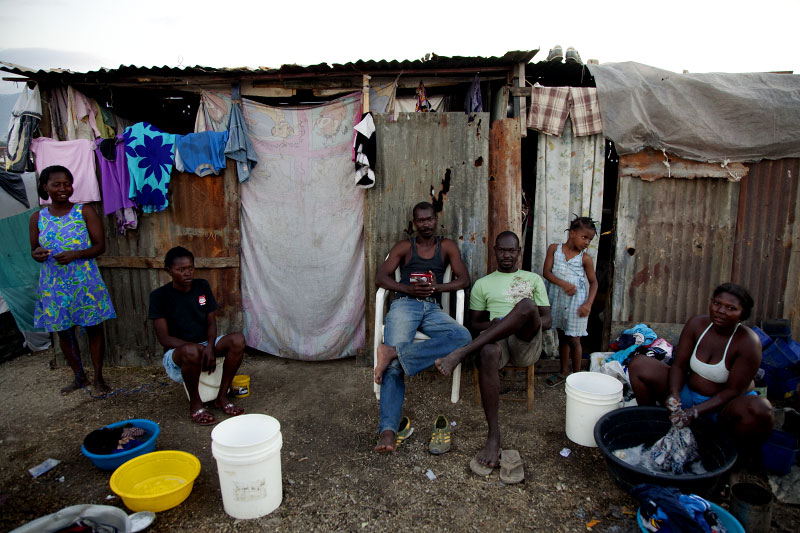 At Pont-Rouge refugee camp, Haitian earthquake survivors of the Joseph Jean Wilguins family stay in front of their shelter.