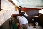 At Pont-Rouge refugee camp, 38 year old Haitian earthquake survivor Jean Enel Montinor holds a hen, as his 29 year old wife Erline stays nearby in his tent where 8 family members live together. The hen is not for the eating. It has a name of {quote}Lina,{quote} and treated as a family member, as Jean Enel lost his mother and father due to the quake.