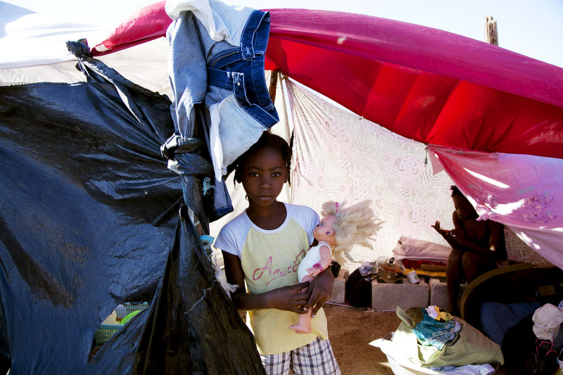 At Pont-Rouge refugee camp, 9 year old Haitian earthquake survivor Sherley Hogsylin holds a doll, as her relative stays nearby in her tent where 6 family members live together.