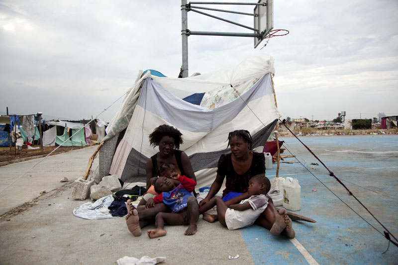 Belene Louis, 25 year old Haitian earthquake IDP, on the left, holds her babies --from the front  Pelerin-Rap, 4, and Clarin, 10 moths -- and her 17 year old relative Jhowanne holds Belene's 5 year old son Jeansky in front of their tent at Pont-Rouge refugee camp.