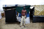 At Pont-Rouge refugee camp, Claudel Louimas, 52 year old Haitian earthquake IDP, stands in front of his tent where he and his 3 children and wife live together. He lost two cousins due to the January 12th quake.