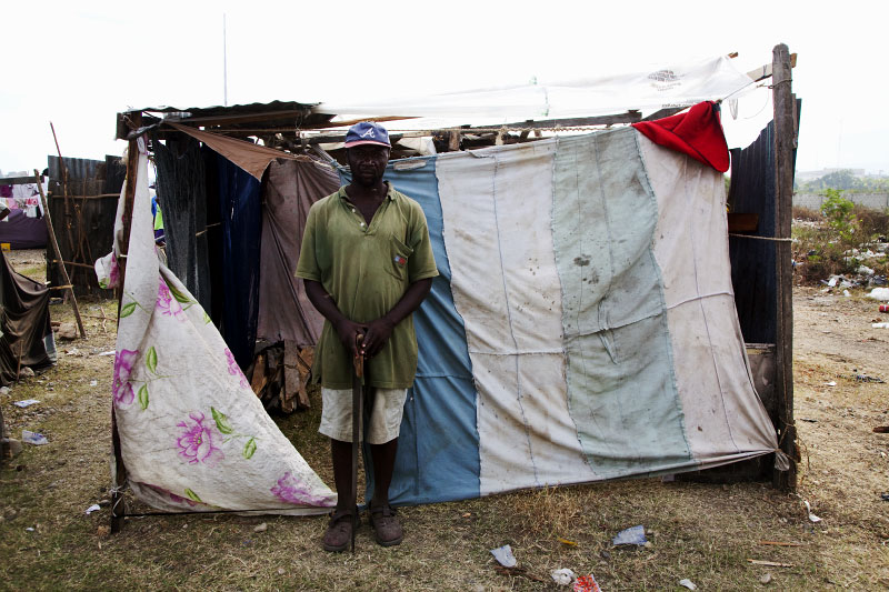 At Pont-Rouge refugee camp, holding a saw, Luckner Naveau, 40 year old Haitian earthquake IDP, stays in front of his shelter where he lives with other 4 family members.