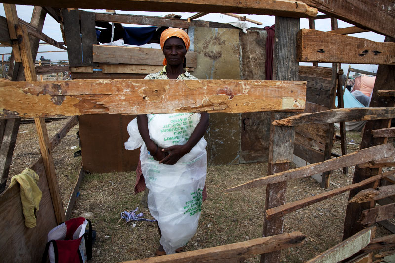 Rapping the plastic sheets for shelter coverage around her body, Alimene Noel, 45 year old Haitian earthquake IDP, stays inside the still working shelter at Pong-Rouge refugee camp.
