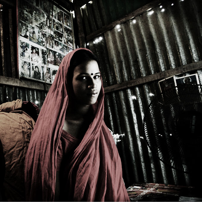 Waiting for customers, 20 year old sex worker Asha stays at her working place and home at Doulabdia brothel District on the bank of the river Jamuna. Many sex workers, like her,  has the occupation by nature, since they were born and grown up at the brothel. Doulabdia, Bangladesh, July 2006.
