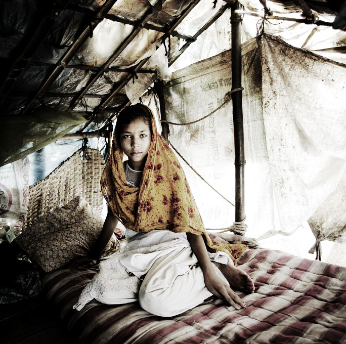 In Dhaka, 12 year-old sex-worker Sumi sits in her working home. Most her female neighbors are sex-workers due to extreme poverty.