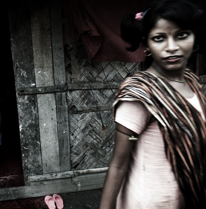 In Bani Shanta, a sex-worker passes through in front of a brothel, waiting for customers. Bani Shanta is a 600 or 700 hundred populated port village in Pashur river and more than half of the residents are sex-workers, making the life of the village dependant on prostitution job. Although in Bangladesh prostitution is legal -- anyone can become sex-worker if over 18 --, some of Bani Shanta's workers are children and victims of human trafficking. In addition, many of such sex-workers have children as single mother, and those kids have nearly no future except becoming prostitutes, pimps or drug dealers, since they are likely to grow in the same circumstances without going to school. Bani Shanta, Bangladesh, July 06 2006.