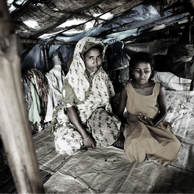 In Dhaka, 35 year-old mother Shima and her 10 y-old daughter Shinur, both sex-workers, sit in their working home. Most their female neighbors are sex-workers due to extreme poverty.