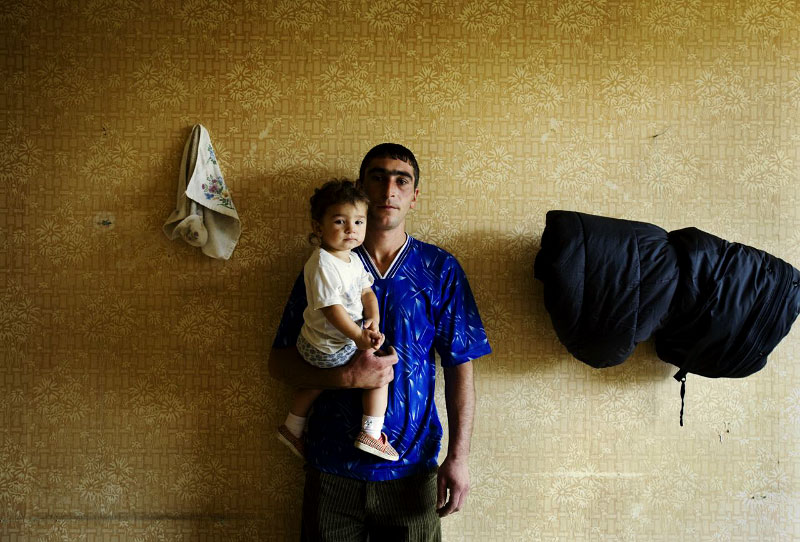 Newly arrived internally displaced family from Pirsnes village of Gori district -- Zviad Buchukuri, 27, and his 18 month-old daughter Maria -- stay at a former Soviet military compound in Tbilisi, the capital of Georgia, as Russian troops continue to occupy large parts of the country. Aug 18, 2008.