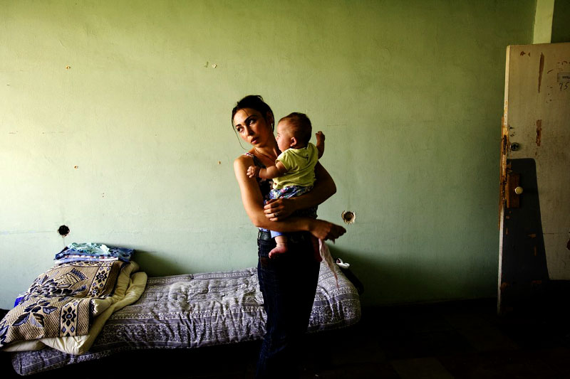 A newly arrived internal displaced person from Khidistava village of Gori -- Natia Shoshiashvili, 27, holding her 4 month old niece Maria  --, stays at a former Soviet's military compound in Tbisili, the capital of Georgia, as Russian troops  still occupies a large part of the country. Aug 17 2008.
