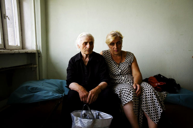 Newly arrived internally displaced people -- Maro Babucidze, 70, from Tskhinvali in South Ossetia, on the left, and Iveli Masmishvili, 44, from Tirdznisi village of Gori district -- stay at a former Soviet military compound in Tbilisi, the capital of Georgia, as Russian troops continue to occupy large parts of the country. Aug 17, 2008.