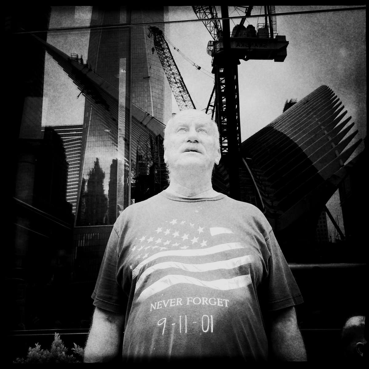 Tyrone McClave, 64, from Pennsylvania keeps looking at the Ground Zero, on the 13th anniversary of September 11th, as Freedom Tower and other under-construction buildings are reflected on a huge glass wall behind him. He said {quote}I come every year.{quote}