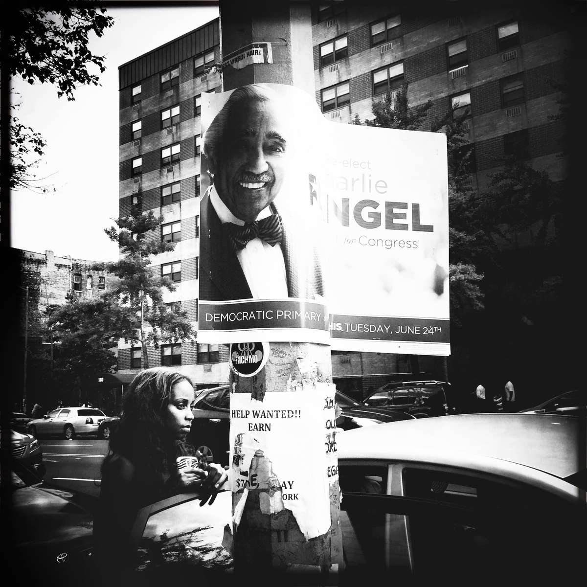 A woman near Congressman Charles Rangel's campaigning poster in Harlem, New York, as the community is changing radically. This was shot on Sunday, June 22 2014. Yet today i want to post because of the primary day.