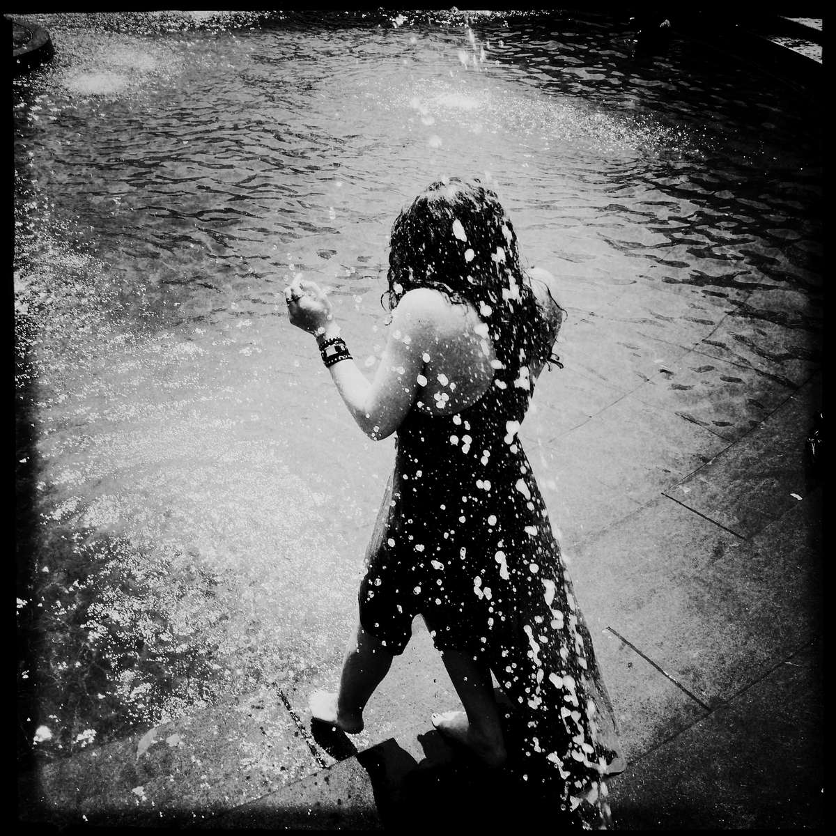 Splash on a girl in Washington Sq Park during a hot summer.