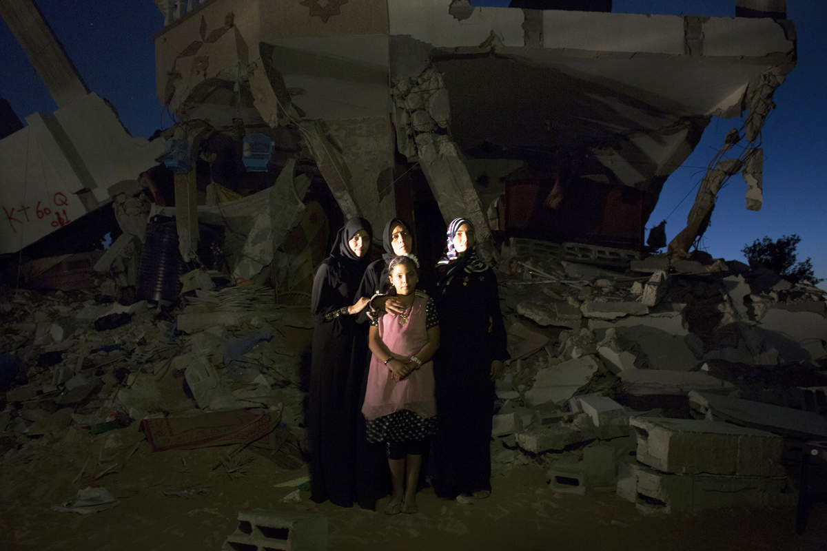 Centering extremely exhausted mother Fatma Ibrahem Abu Mutlag, 46, her daughters -- Heba, 23, on the left, Hanadi, 19, on the right, and Hadeel, 9, on the front -- pose at their destroyed home in Khan Yunis due to Israeli airstrike and bulldozers during the summer's 50-day war between Israel and Hamas. Despite the serious damage, they cannot leave, since there is no place else for them to move, or too expensive for the rent after the war. Khoza'a in Khan Yunis, Gaza. Oct/05/2014