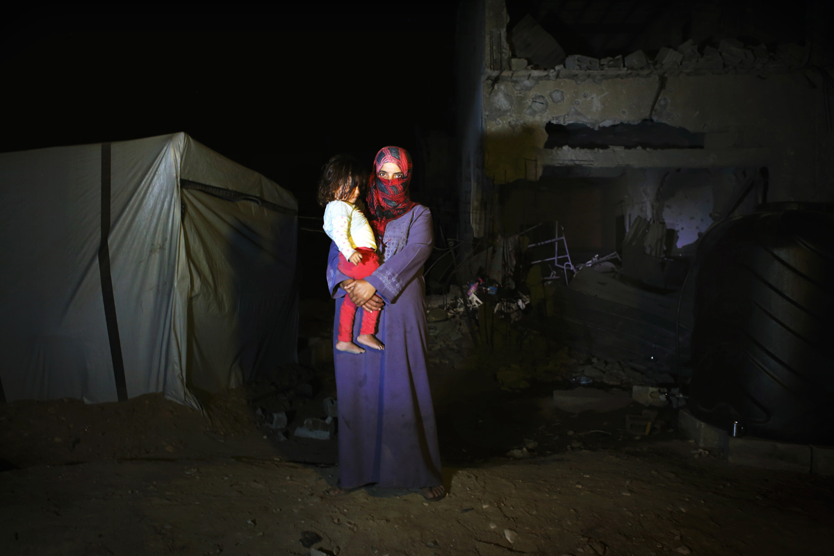 26 years old mother Heba Fareed Abu Jama'a and her daughter Moha Hussein, 2 years and 3 months, pose at their destroyed house due to Israeli attack during the summer's 50 day war between Hamas. Since there is no space to move, or too expensive to do so, they have to live at a tent next to the house, with 8 other persons.Al-Zana'a in Khan Yunis, Gaza, Oct 08, 2014.