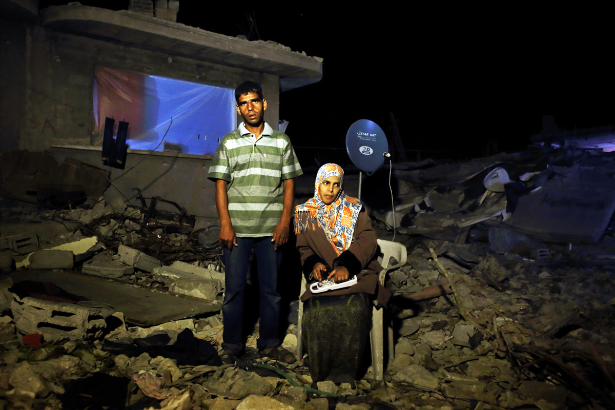 Assan Mohamed Najar, 30, and his 9 month pregnant and blind wife Tahreer Adnan Najar, 27, pose at their destroyed home in Khan Yunis due to Israeli artillery and airstrike during the summer's 50-day war between Israel and Hamas. Despite their difficult and dangerous condition, they have to stay in the destroyed house, since there is no place else for them to move, or too expensive to do so. Khoza'a in Khan Yunis, Gaza. Oct/10/2014