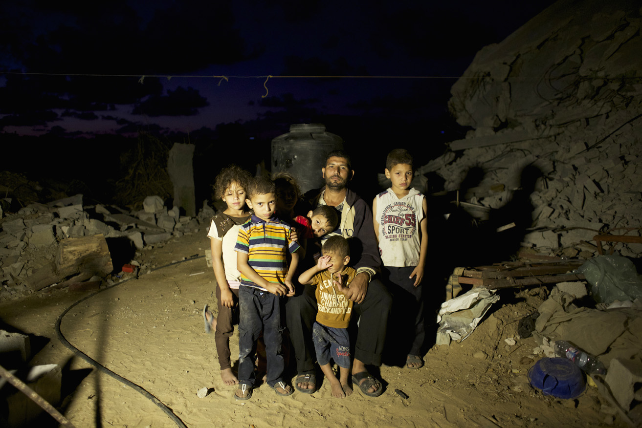 Adil Mohammed Abu Samhan, 42, and his children pose in front their destroyed home in Khan Yunis by Israeli airstrike and bulldozers during the summer's 50-day war between Israel and Hamas. They have to still live at the site, since there is no place else for them to move, or too expensive for the rent after the war. Al-Zana'a in Khan Yunis, Gaza. Oct/03/ 2014