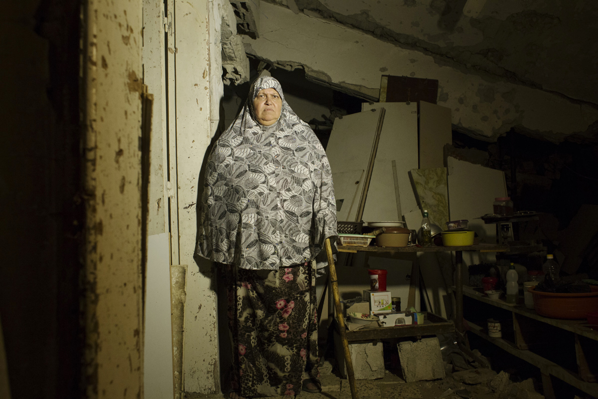Soad Abd Rabo Al-Zaza, 65, despite her paralyzed leg, poses at her destroyed house due to Israeli air strike during the summer's 50 day's war between Israel and Hamas, as she still lives in (with her husband and other family members). Despite the fact the house is in a very dangerous condition -- it further becomes 40 cm down recently, there is no place to move, and virtually nobody has come to help yet. Alshjaia, Gaza, Oct 06, 2014.