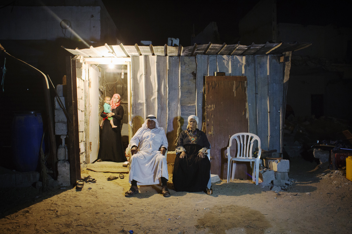 At a shack, Salman Saliman Abu Mutlag, 80, and his wife Marym Hmdan, 67, their grand daughter Hchhtam, 24, and 1 year and half old grand-grand son Qosay pose. They still have to live at their destroyed home compound in Khan Yunis due to Israeli artilleries and bulldozers during the summer's 50-day war between Israel and Hamas. They cannot leave, since there is no place else for them to move, or too expensive for the rent after the war. Khoza'a in Khan Yunis, Gaza. Oct/05/2014