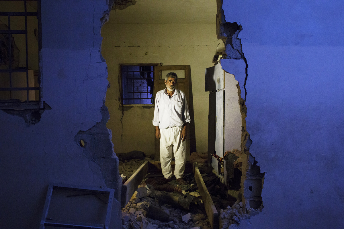 Mohamed Abu Jama'a, 56, poses at his home in Khan Yunis destroyed by Israeli artillery during the summer's 50-day war between Israel and Hamas. Despite the serious damage, he cannot leave, since there is no place else for him to move, or too expensive for the rent after the war. Al-Zana'a in Khan Yunis, Gaza, Oct 08, 2014.