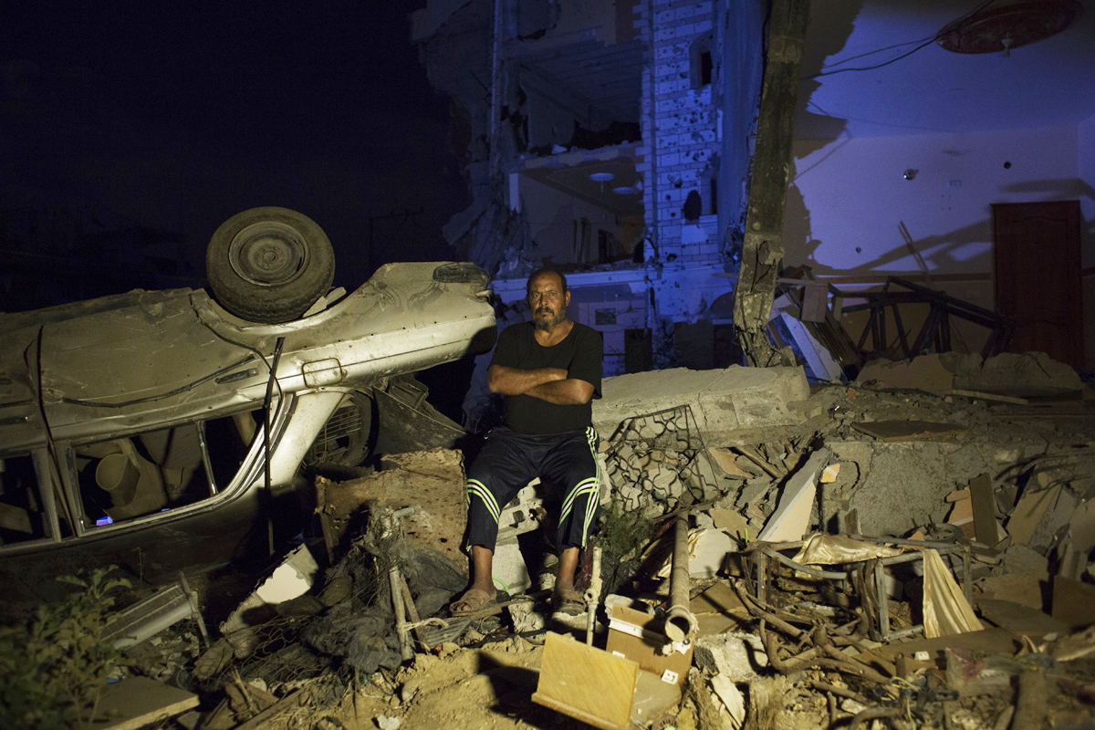 55 year old taxi driver Mohamed Abu Jama'a poses next to his  destroyed mercedes taxi and home in Khan Yunis due to Israeli airstrike and bulldozers during the summer's 50-day war between Israel and Hamas. He has to still live at the site, since there is no place else for him to move, or too expensive for the rent after the war. Al-Zana'a in Khan Yunis, Gaza. Oct/08/2014