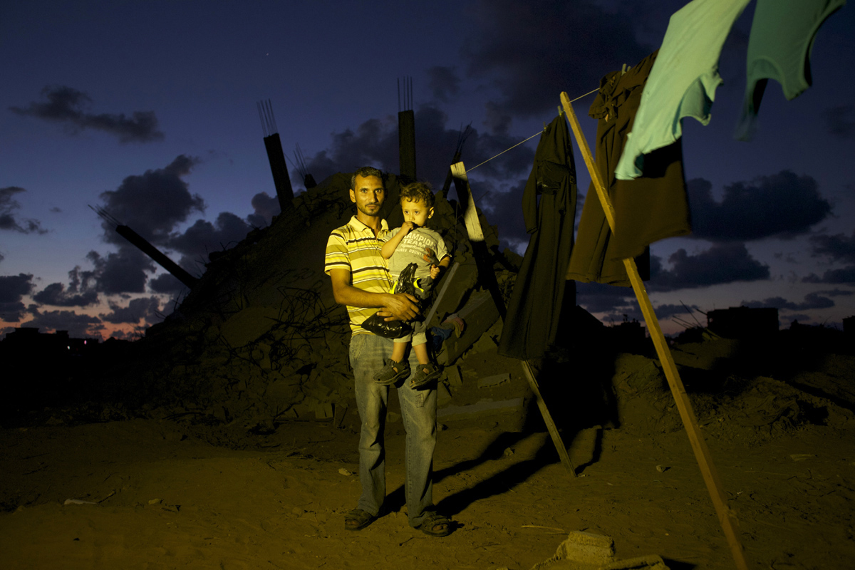 Mohamed Abu Samhain, 26, and his 2 year old son Rain Mohammed Samhain pose in front their destroyed home in Khan Yunis by Israeli airstrike and bulldozers during the summer's 50-day war between Israel and Hamas. They have to still live at the site, since there is no place else for them to move, or too expensive for the rent after the war. Al-Zana'a in Khan Yunis, Gaza.