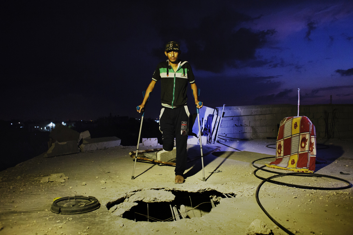 20 years old amputee Ameer Abu Jama'a hit by Israeli artillery during the summer's 50 day war between Israel and Hamas poses at the rooftop of his destroyed home, due to Israel shelling.Al-Zana'a in Khan Yunis, Gaza, Oct 08, 2014.
