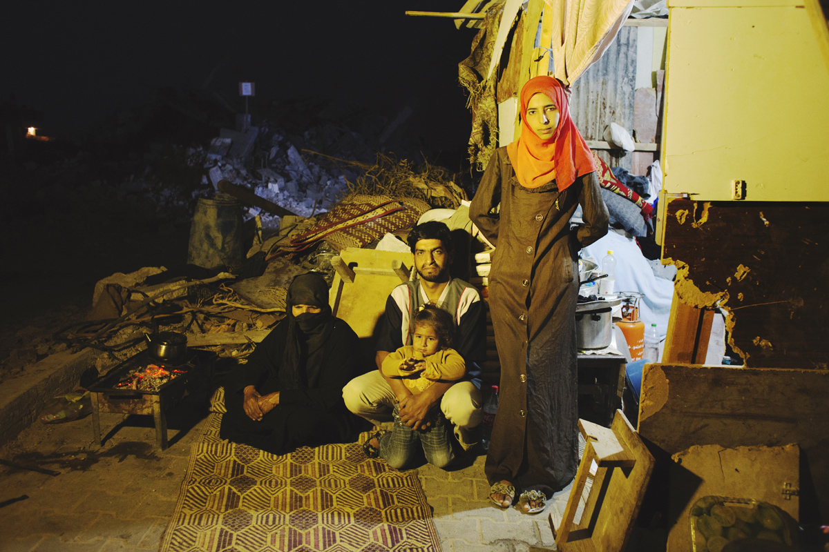 Fadla Al-Najar, 63, and his 30 year old son Osama and her 2 year old grand-daughter Habiba, and Osama' s 26 year old wife Taghreed, on the right, saw their home in Khoza'a in Khan Yunis destroyed by Israel Defense Forces during the summer's 50-day war between Israel and Hamas. They still stay in a tent on the site of the damaged home. Despite the difficulty, they cannot leave, since there is no other place to move, or too expensive. And virtually nobody has come to help yet. Oct/10/2014