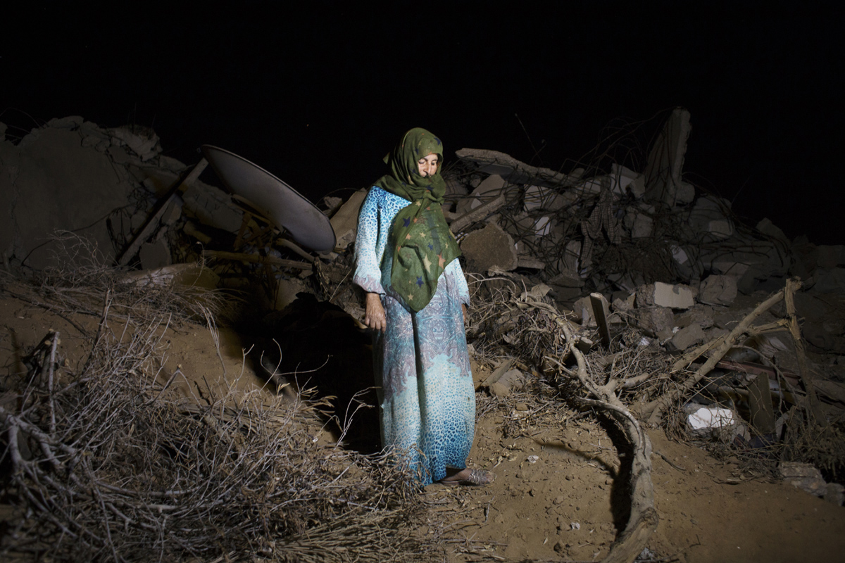 Sabeeha Abu Rouk, 60, at her destroyed home in Khan Yunis by Israeli airstrike and bulldozers during the summer's 50-day war between Israel and Hamas. She stays at the site with her family embers, since there is no place else for them to move, or too expensive for the rent after the war. Khoza'a in Khan Yunis, Gaza. Oct/05/2014