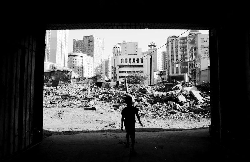An Uighur boy stays at an entrance of a barely left building in a destroyed Uighur community area in Urumqi, Xinjiang, but his building could face the demolition soon due to the Chinese modernization projects or Chinesefication, though the government insists the main reason is security of houses -- especially resistance to earthquake.