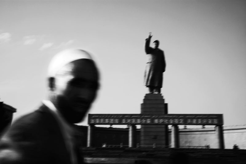 An Uighur man passes in front of a stature of Mao in Kashgar, Xinjiang, as the Chinese modernization projects or Chinesefication expand into the province.
