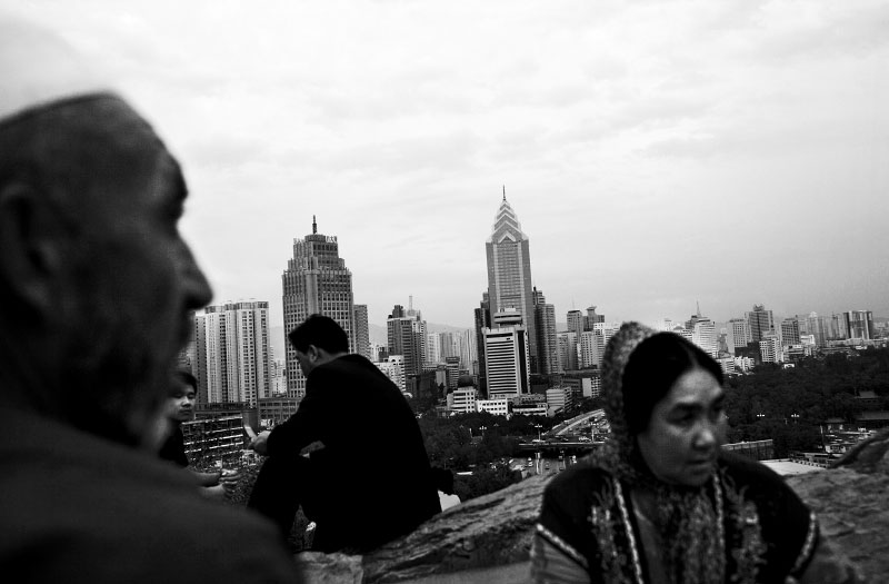 A Uighur couple and two Han Chinese men at an Urumqi park overlooking the province capital's new buildings.