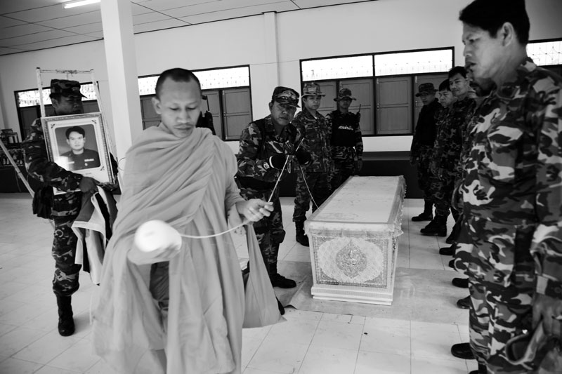 With a help of a monk, Thai soldiers prepare for a funeral of their colleague, who was killed allegedly by Muslim separatist insurgents in Yala Province in South Thailand where the majority is Muslims and a large number of its people look for the independence or federation with Malaysia. April 04, 2008, Yala, Thailand.