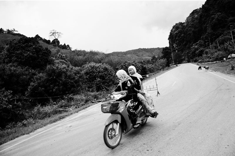 Muslim women on motorbike pass through a mountain area of Taluayia village in Yaha in Yala Province in South Thailand where people face separatist militant attacks. April 07, 2008, Yaha, Thailand.