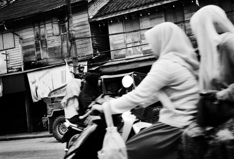 Thai Muslim women on motor bikes pass through, while a Thai solider is on the duty of patrol in Rueso in South Thailand where the majority is Muslims and they are often in poverty compared to Thai Buddhists. Due to the strong Buddhism identity of Thailand, many southern Muslims feel themselves in limbo and a certain number of the people look for the independence or joining together with Malaysia. Unfortunately the bloody separate insurgency continues. April 12 2008, Rueso, Thailand.