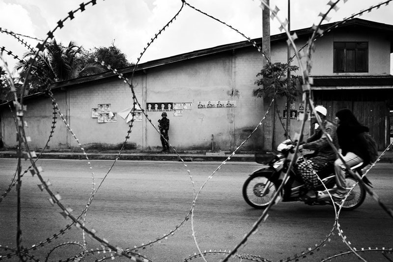 Thai soldier takes the cover near a checkpoint, while Muslims on a motorbike passes through in Rueso in South Thailand where the majority is Muslims and they are often in poverty compared to Thai Buddhists. Due to the strong Buddhism identity of Thailand, many southern Muslims feel themselves in limbo and a certain number of the people look for the independence or joining together with Malaysia. Unfortunately the bloody separate insurgency continues. April 12 2008, Rueso, Thailand.