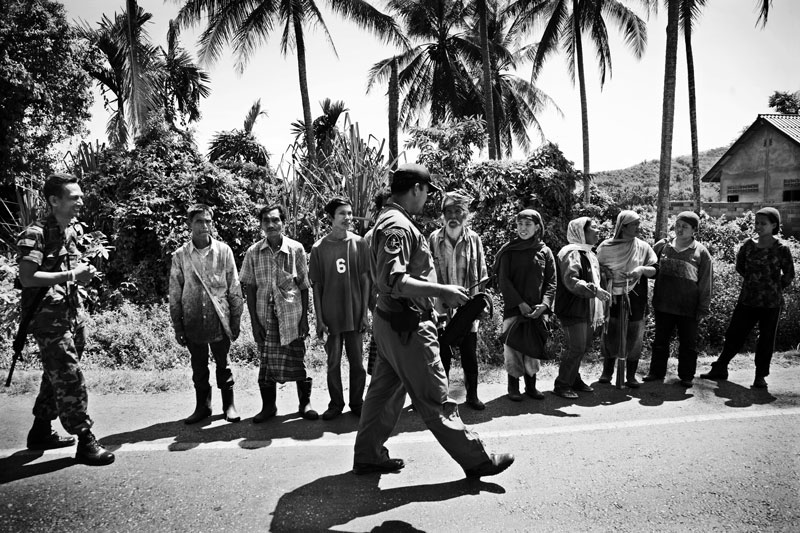 After a bomb explosion, farmers are forced to line up by the government soldiers to be inquired about the suspect, in Yala province in South Thailand, where the majority is Muslims and Muslim separate insurgency continues. April 08 2008, Thailand.