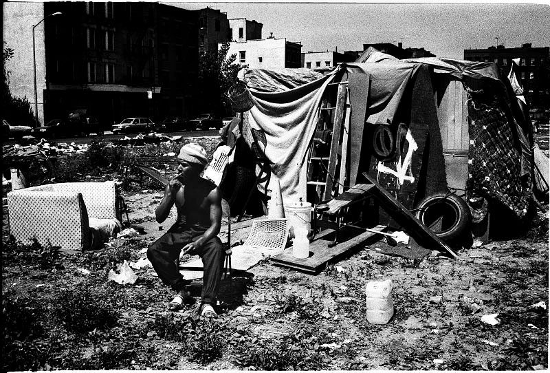 A homeless man is squatting at an empty lot in Alphabet City, while there is a lack of affordable housing and many homeless do not like to go to shelter due to security and non-privacy reasons. New York, June 1991.