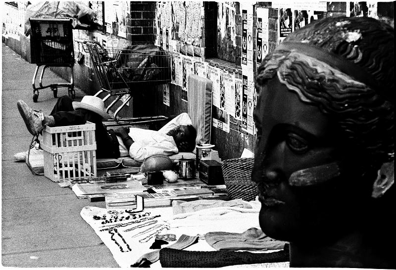 A homeless man is lying in the street, waiting for customers to buy his junk-like commodities. New York, June 1991.