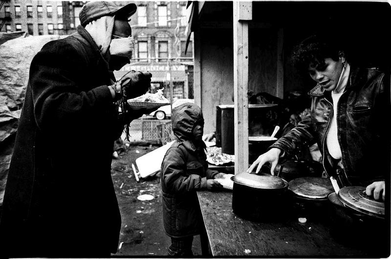 Homeless men, including a child, take Christmas meal at the soup kitchen of an empty lot called La Plaza. December 25 1987.