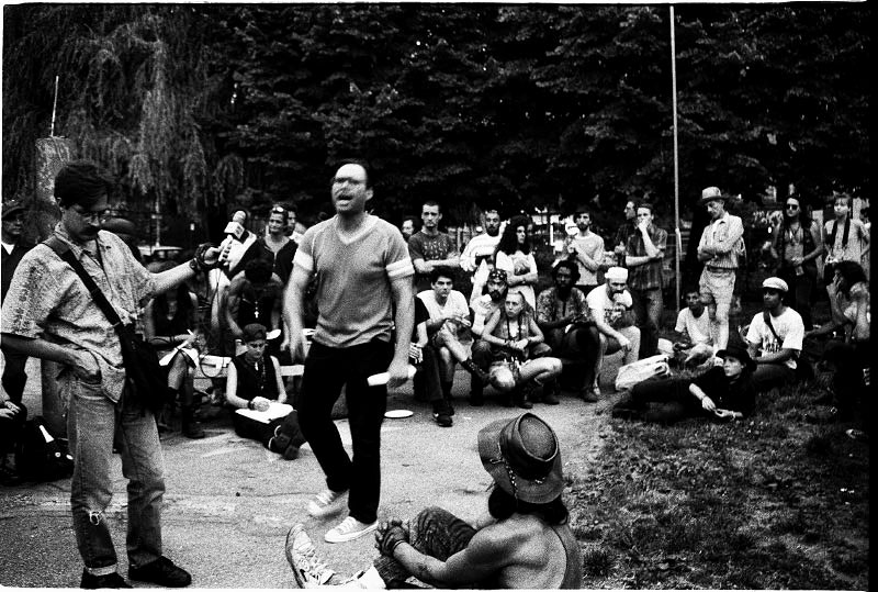 Art, a squatter and one of Tompkins Sq Activists, speaks out for how to fight to protect their human rights, while Paul, a reporter of WBAI, documents the speech, and homeless people, squatters, and supporters listen to him. New York, Very later afternoon in June 03(?), 1991.