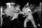 Just outside Tompkins Sq Park, a riot geared policeman and three undercover officers are about violently to arrest a homeless-rights activist who was hitting a trash can as drum. Many human rights advocates had criticized NYPD for the use of excessive force as it confronted Tompkins protesters. New York, July 1989.