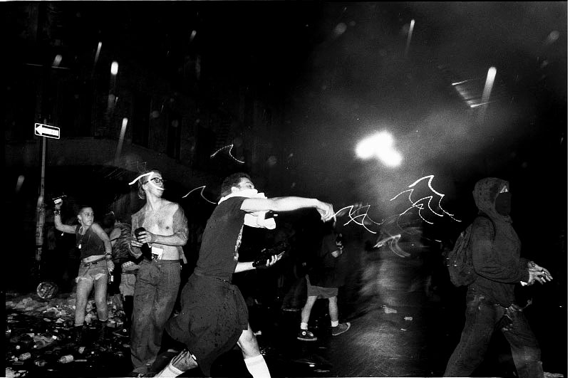 In Avenue A, in front of the Tompkins Square Park, anti-gentrification protesters hurl bottles at the riot-geared police forces. New York, May 27, 1991.