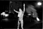 During a protest in the Tompkins Square Park, a protester indicates double insulting signs at NYPD's riot geared forces. His being naked is also an intentional protest, since NYPD, then, is recognized very brutal by many residents of the community. New York, May 27, 1991.