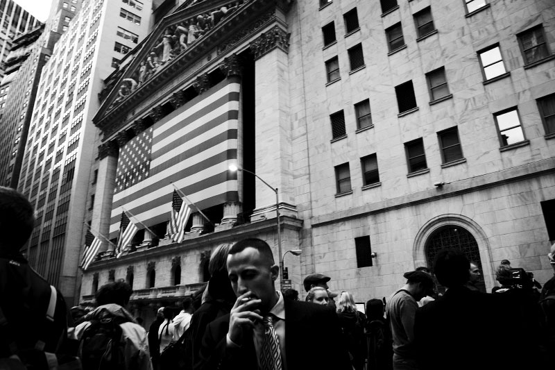 With smoking, a trader gets out of the New York Stock Exchange Market after the closing bell, while the media and others  crowd due the another extraordinary and traumatic session Monday, and people of the Main Street also start to worry about the impact. The Dow Jones industrials plunged as much as 800 points -- their largest one-day point drop -- before recovering to close with a loss of 370, resulting in the Dow below 10,000 for the first time in four years, despite the US and other states' government efforts to contain the fast-spreading financial crisis. New York, Oct 06 2008.