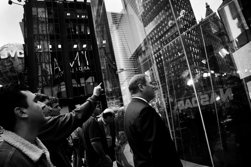 People watch the financial news at the Nasdaq site in the Times Square, as Wall Street suffers through another extraordinary and traumatic session Monday, and people of the Main Street also start to worry about the impact. The Dow Jones industrials plunged as much as 800 points -- their largest one-day point drop -- before recovering to close with a loss of 370, resulting in the Dow below 10,000 for the first time in four years, despite the US and other states' government efforts to contain the fast-spreading financial crisis. New York, Oct 06 2008.