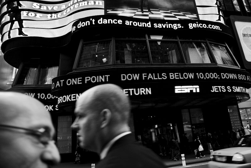 Men walk in front of the Times Square news ticker flashing information about the Dow dropping below 10,000 Monday. Following a big drop of the Asian Markets, the Dow Jones industrials plunged as much as 800 points -- their largest one-day point drop -- before recovering to close with a loss of 370, resulting in the Dow below 10,000 for the first time in four years, despite the US and other states' government efforts to contain the fast-spreading financial crisis. New York, Oct 06 2008.