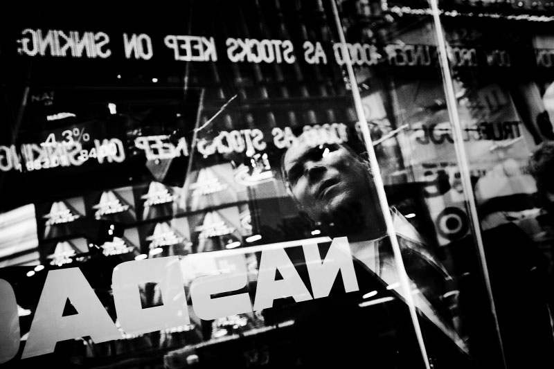 A man is reflected on the Nasdaq site in the Times Square, watching the financial news, as Wall Street suffers through another extraordinary and traumatic session Monday, and people of the Main Street also start to worry about the impact. The Dow Jones industrials plunged as much as 800 points -- their largest one-day point drop -- before recovering to close with a loss of 370, resulting in the Dow below 10,000 for the first time in four years, despite the US and other states' government efforts to contain the fast-spreading financial crisis. New York, Oct 06 2008.