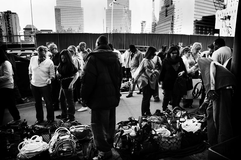Vendors sell counterfeits of brand bags, such as of Gucci, Louis Vuitton , Prada, Hermes, etc, in front of the former World Trader center site. Their business seems ok at the moment, while big corporations, especially financial industry, suffer due to the economic crisis. Yet at the same time, nobody knows how deep and how far the current crisis will expand. New York, Oct 11 2008.