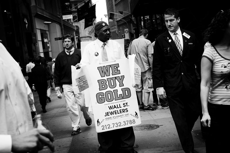 In Wall street, a man holds a placard of {quote} We Buy Gold{quote}, as gold pricehas increased due to the current financial crisis or economic melt-down.New York, Oct 13 2008.